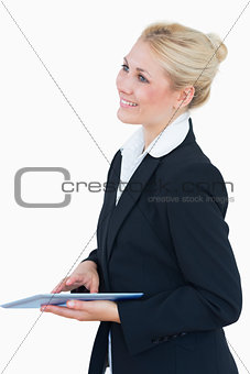 Smiling business woman with digital tablet looking away