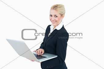 Portrait of happy young businesswoman using laptop