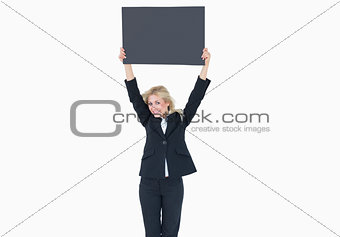 Portrait of young business woman holding up empty banner