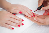 Woman applying nail varnish to finger nails