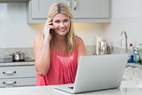 Happy woman using laptop while on call in the kitchen