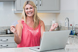Excited woman with clenched fists using laptop in the kitchen