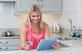Woman doing online shopping on digital tablet in the kitchen