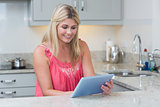 Casual woman using digital tablet in the kitchen