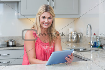 Portrait of casual woman using digital tablet in the kitchen