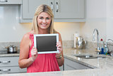 Portrait of casual woman holding digital tablet in kitchen