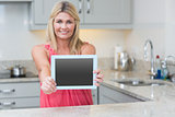 Portrait of casual woman holding out digital tablet in kitchen