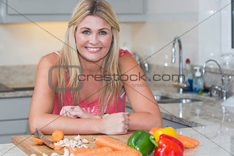 Portrait of smiling woman with vegetables in kitchen