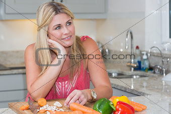 Thoughtful woman with vegetables in the kitchen