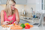 Woman cooking whilst looking at laptop