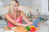 Woman cooking whilst looking at digital tablet in kitchen