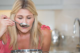 Young woman tasting food in kitchen
