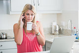 Woman with laptop and coffee cup on call in kitchen