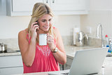 Happy woman with laptop and coffee cup on call in kitchen
