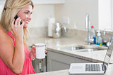 Happy woman with laptop and coffee cup on call in the kitchen