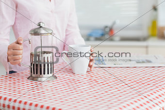 Woman with kettle and coffee cup