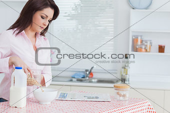 Woman pouring cereal in bowl