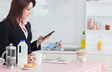 Business woman text messaging while having breakfast in kitchen