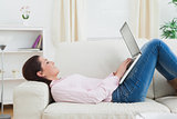 Happy woman lying on sofa and using laptop