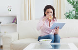 Woman drinking wine while using digital tablet at home