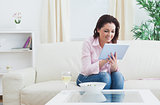 Woman with wine and bowl using digital tablet on sofa