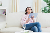Casual cheerful woman using digital tablet on sofa