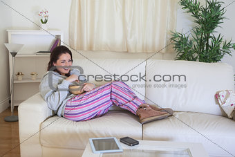 Happy woman on couch with bowl at home