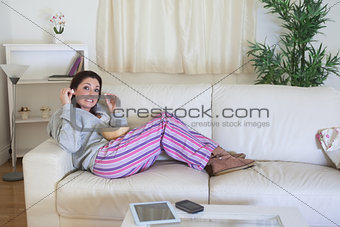 Bored woman having popcorn on couch at home