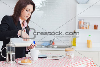 Business woman pouring milk in coffee cup