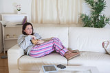 Relaxed woman with popcorn bowl watching tv