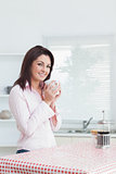 Smiling woman with cup of coffee in the kitchen