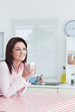 Happy woman looks away with coffee cup in hands