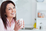 Cheerful woman looking away while drinking coffee