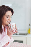 Woman with eyes closed smelling coffee