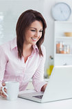 Happy woman with coffee cup using laptop