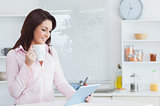 Woman with coffee cup looking at digital tablet