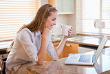 Happy woman with coffee cup looking at laptop