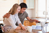 Young couple looking laptop screen