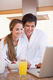 Couple using laptop over breakfast