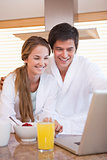 Couple using laptop over breakfast