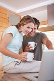 Couple using laptop while drinking coffee