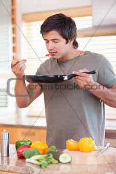 Young man smelling food in the kitchen