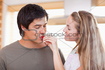 Woman feeding vegetable to man