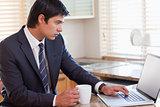Business man using laptop while having coffee