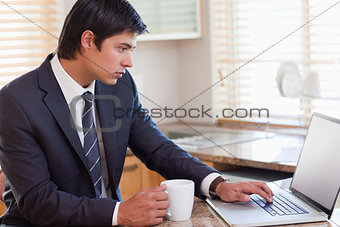 Business man using laptop while having coffee