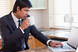 Business man using laptop while drinking coffee
