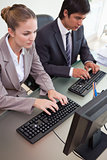 Business colleagues using computers in office
