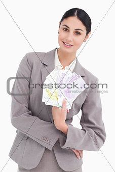 Portrait of business woman holding fanned banknotes