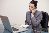 Business woman using laptop while on call