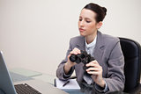 Business woman with binoculars looking at laptop